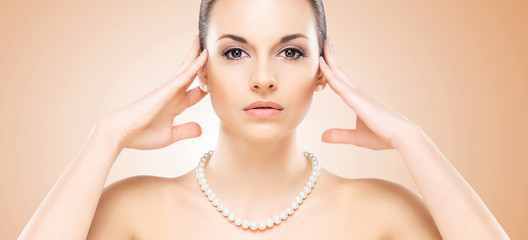 Portrait of young, beautiful and healthy woman in a pearl neckla