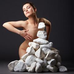 Telekinesis. Inspired nude woman with stones