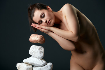Woman with closed eyes moving stones by thought