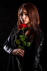 Beautiful young woman with a red rose in a black leather jacket