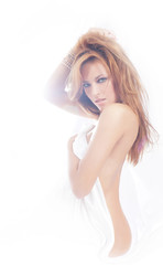 Fashion image of young and sexy redhead woman in white lingerie