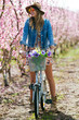 Beautiful young woman with a vintage bike in the field.