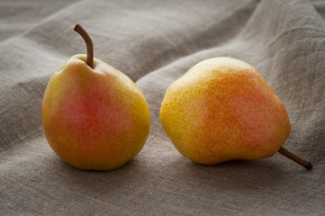 Art still life with small red pears on hessian linen fabric