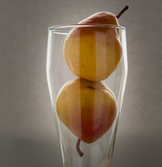 Art still life with small red pears in glass on hessian linen