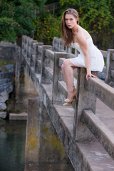Cute young woman in white dress sitting on side of bridge