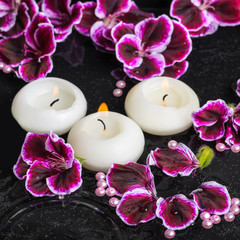 beautiful spa still life of geranium flower and candles in rippl