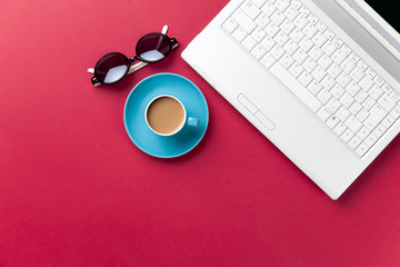 Sunglasses and cup of coffee near notebook