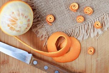 orange on table with peel curls