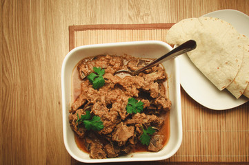 Lamb mutton Korma on a wooden background