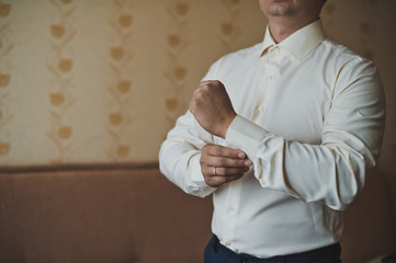 The young man dresses cuff links on a shirt 2258.