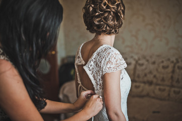 The girlfriend helps the bride to dress a wedding dress 2298.