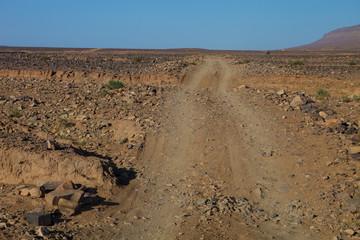 cars resurfacing tracks in the stony desert, Morocco