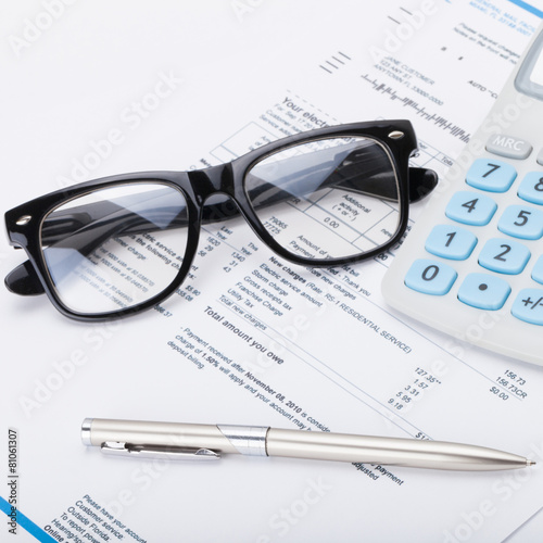 Calculator with pen, glasses and utility bill - close up shot