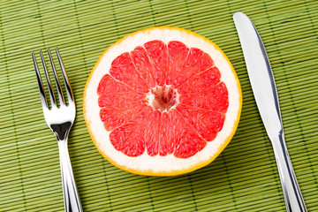 Grapefruit between fork and knife
