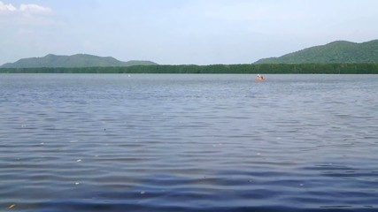 People rowing rowboat in the lake. background is the mountain