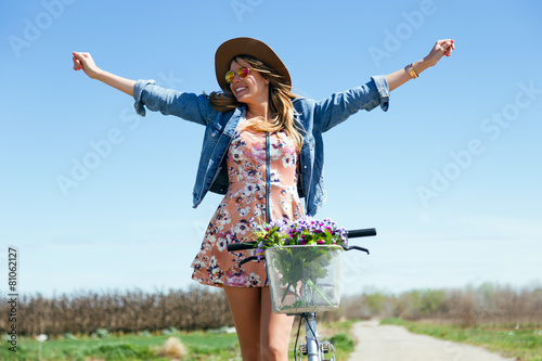 Beautiful young woman with a vintage bike in the field. - 81062127