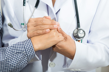 Medical doctor holding senior patient's hands