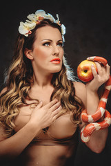 Sexy beautiful woman with red apple and snake
