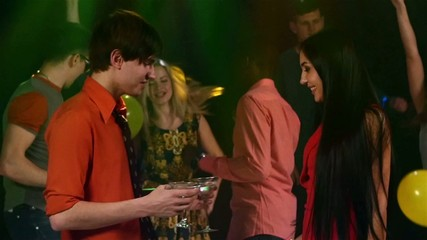 Party: A young man brings girl in a red dress with  glass of
