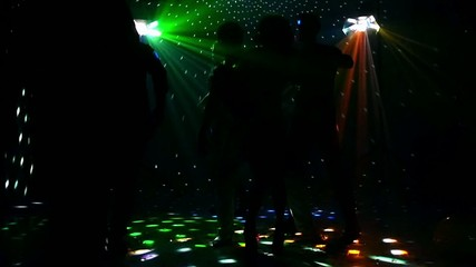 Girl and guy dancing in glow of LED spotlights. company friends