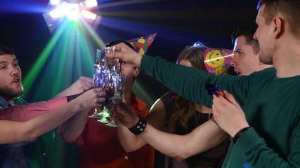 Nightclub : company of friends  party and dancing clink glasses