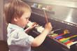 Leinwanddruck Bild - Young boy painting piano keys. Fine arts and music.