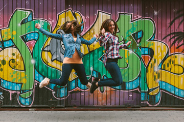 Two Cheerful Women Jumping in the Air