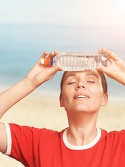 Woman holding a cold water bottle on her forehead. Eyes closed.