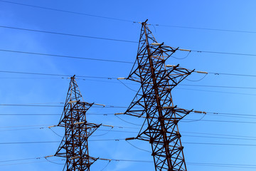 Two pillars of electric transmission lines against the blue sky