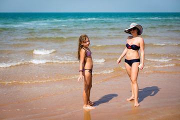 tanned woman and a girl standing on the beach