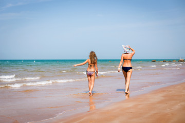 tanned woman and a girl walking on the seashore