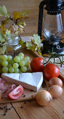 Cheese, bread, onions, wine, tomatoes and a kerosene lamp