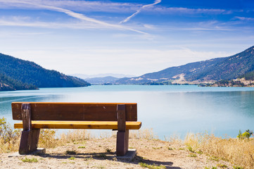 Park bench overlooking blue lake