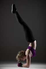 Beautiful sporty girl doing handstand