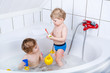 Two little sibling boys having fun with water by taking bath in