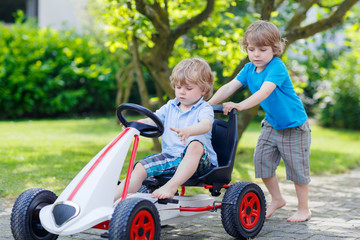 Two happy sibling boys having fun with toy car