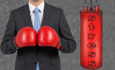 businessman wearing boxing gloves is ready to hit punching bag
