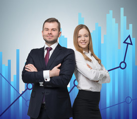 A young business couple are standing over the graph background.