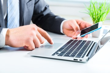 Banking. Businessman using laptop and mobile phone