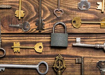 Locksmith. Check-lock and different keys on wooden background