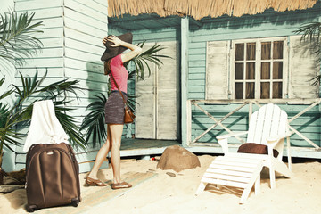 The young slender girl, happy examines bungalows on the island