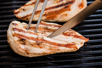 Grilled chicken breast fillets on BBQ with fork and knife