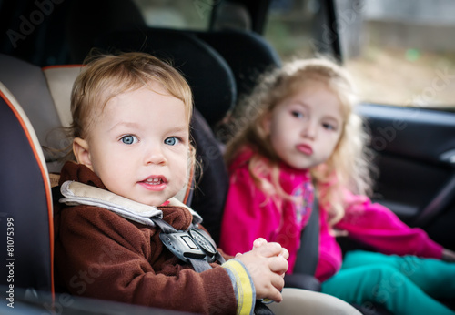 small children in car seats in the car - 81075399
