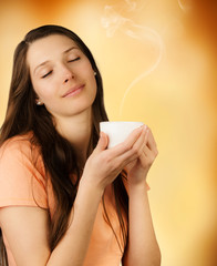 Attractive young brunette woman holding cup of coffee
