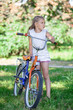 Preteen Caucasian girl standing in summer park with cycle