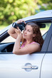 Young woman sitting in car, takes pictures with digital camera
