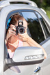 Caucasian woman with slr camera photographing from vehicle