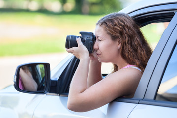 Driver photographer shoots slr camera while sits inside vehicle