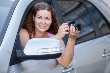 Caucasian woman with digital camera sitting in her car