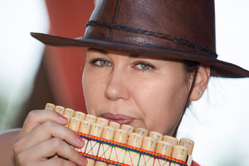 Young country woman in cowboy hat playing the panpipe